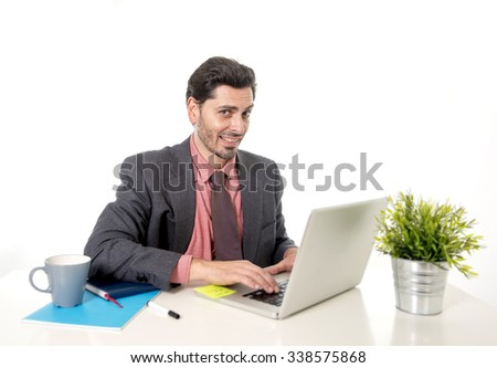 young attractive Latin businessman in suit and tie working at office computer desk  typing on the laptop looking happy and successful in business concept - stock photo