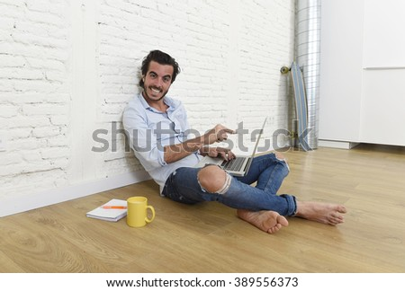 young attractive latin man in hipster and modern casual style look sitting happy on unfurnished living room home floor working on laptop computer drinking coffee in internet concept