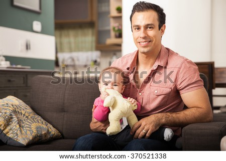 Young attractive Latin man spending time with her baby girl at home - stock photo