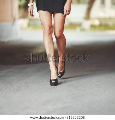 Young attractive legs of young pretty woman walking next to you.  - stock photo
