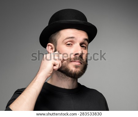 Young attractive macho stylish fashionable guy.  portrait on gray background. a man in a black hat with a beard mustache curls. concept of narcissism - stock photo