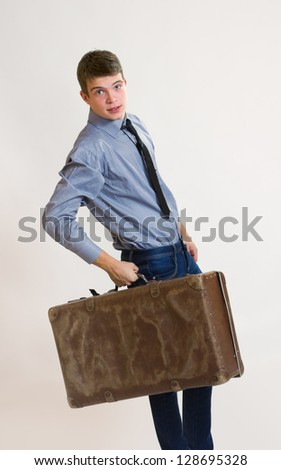 Young attractive male - businessman holding his old suitcase - stock photo