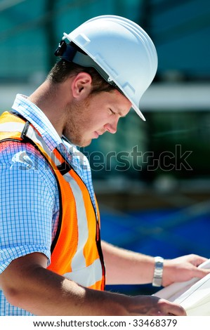 Young Attractive Male Civil Engineer, Checking The Blueprints - stock photo