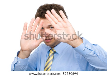 young attractive male cover his face, try to hide, shows keep away from me gesture, studio shoot isolated on white background