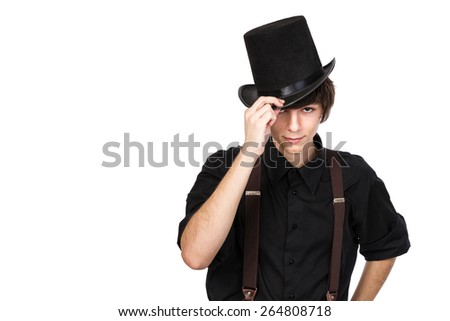 Young attractive male in a black shirt and jeans suspenders, touching the brim of his black top hat in a salute, with a confident and smiling expression on his face, isolated on white - stock photo
