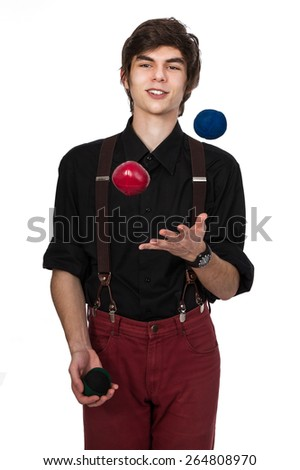 Young attractive male in a black shirt and red jeans with suspenders, juggling three balls with a confident and positive expression on his face, isolated on white - stock photo