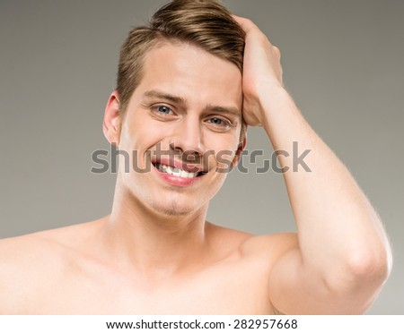 Young attractive male model posing on grey background. Beauty concept. - stock photo