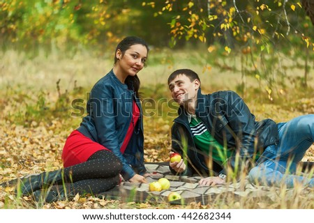 Young attractive man and girl sit on plaid. Autumn picnic rest on nature - stock photo