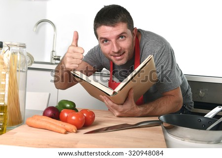 young attractive man at home kitchen reading recipe book smiling happy leaning on table with oil, pasta , vegetables and knife wearing red apron giving thumb up in learning cooking concept - stock photo
