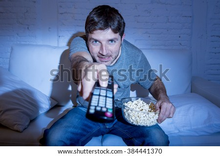 young attractive man at home lying on couch at living room watching tv eating popcorn bowl using remote control and changing channel or volume looking interested and excited in television fan concept - stock photo