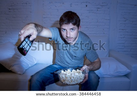young attractive man at home lying on couch at living room watching tv holding remote control and changing channel or volume - stock photo