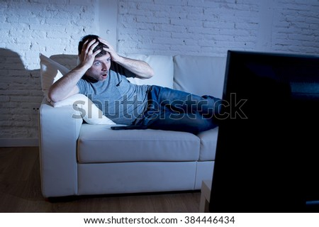 young attractive man at home lying on couch at living room watching tv  looking surprised and in shock maybe with a horror film or disaster breaking news - stock photo
