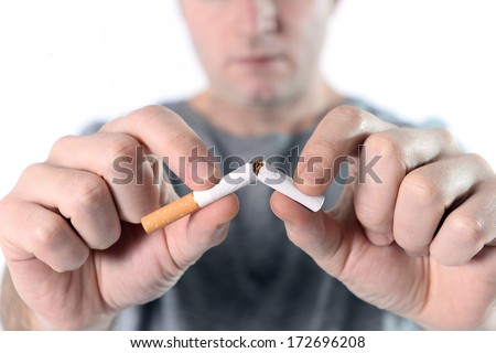 Young attractive man breaking cigarette isolated on white background