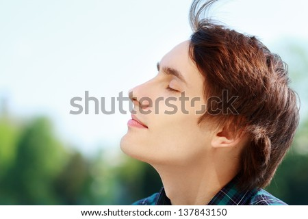 Young attractive man breathing fresh air outdoors showing his face to the wind - stock photo