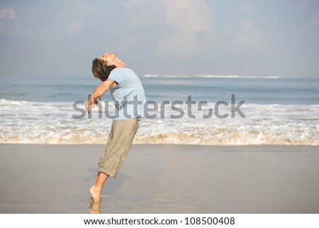 Young attractive man dancing on the beach, bending backwards while on tip toes. - stock photo