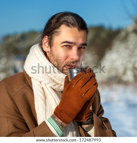 young attractive man drinking tea outside in winter time, close up portrait