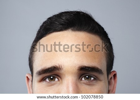 Young attractive man face looking camera - stock photo
