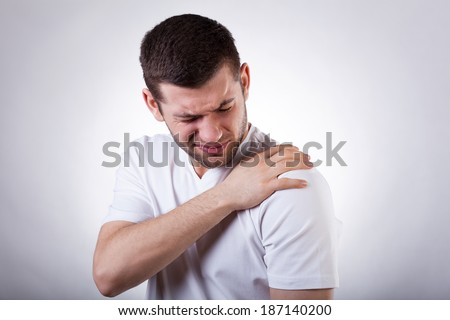 Young attractive man having shoulder pain - stock photo
