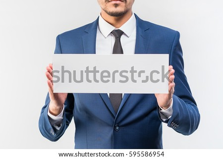 Young attractive man in a blue suit holding a white sign on a white background. Isolated
