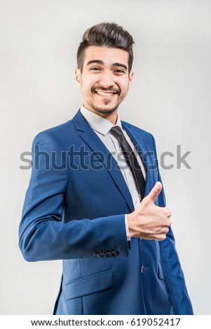 Young attractive man in a blue suit showing thumb up on a gray background. Isolated