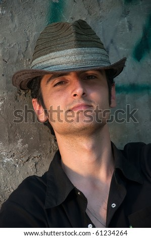 young attractive man in a straw hat against the wall, portrait - stock photo