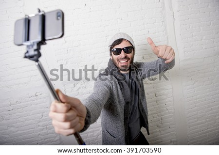 young attractive man in casual clothes beanie hipster style holding selfie stick mobile phone shooting self portrait photo or recording video in internet blog and blogger concept - stock photo