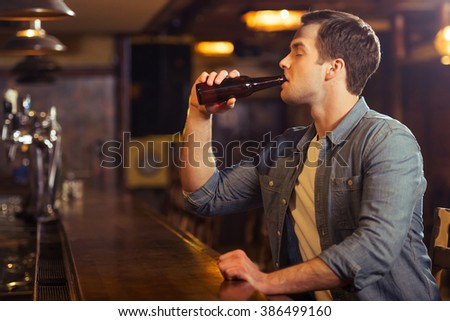 Young attractive man in casual clothes is drinking beer while sitting at bar counter in pub - stock photo