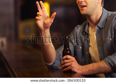 Young attractive man in casual clothes is holding a bottle of beer and making order while sitting at bar counter in pub, close-up - stock photo