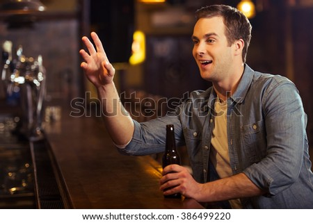 Young attractive man in casual clothes is smiling, holding a bottle of beer and making order while sitting at bar counter in pub - stock photo