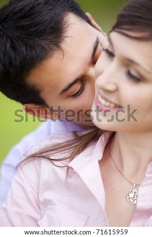 Young attractive man kissing her girlfriend. Focus on him. - stock photo