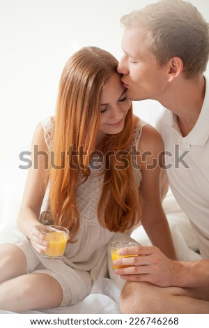 Young attractive man kissing his pretty girlfriend in a forehead - stock photo