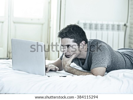 young attractive man lying on bed or couch enjoying social networking using  computer laptop at home wireless connected to internet in technology and modern lifestyle concept - stock photo