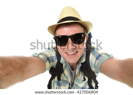 young attractive man or backpacker student taking selfie photo alone with mobile phone or camera wearing sunglasses and summer hat in tourist look smiling happy isolated on white background   - stock photo
