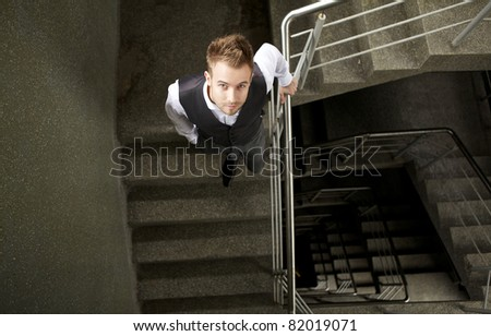 Young attractive man pose on ladder. - stock photo