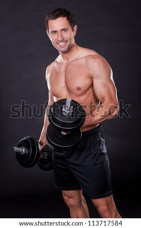 Young Attractive Man Pumping Weights Isolated On Black Background - stock photo