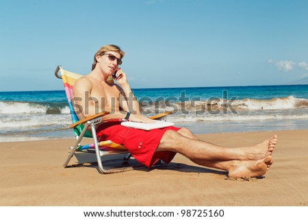 Young Attractive Man Relaxing at the Beach with Cell Phone and Computer