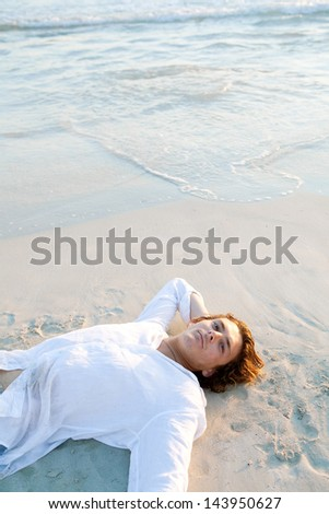 Young attractive man relaxing laying down on the shore of a white sand beach at sunset, with the waves bathing the shore in an idyllic nature location, being thoughtful.
