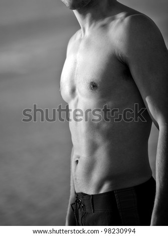 Young attractive man standing at the beach - stock photo