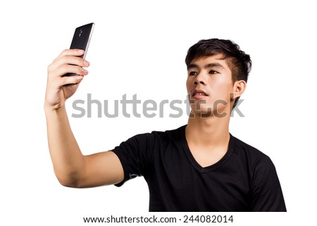 young attractive man taking pictures of him self (selfie) with smartphone isolated on white background.  - stock photo