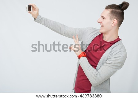 Young attractive man taking selfie with mobile phone standing against grey background. Gesturing and funny face