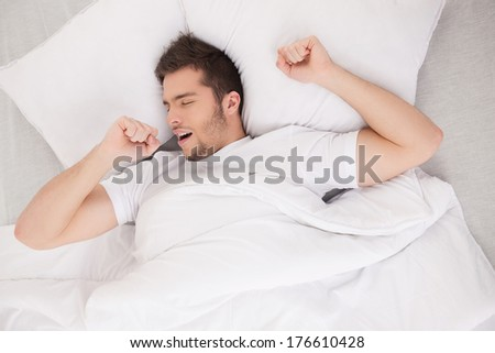 young attractive man waking in morning. handsome guy stretching and yawning in bed - stock photo
