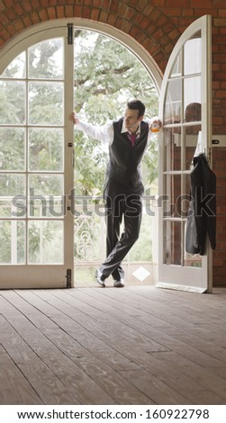 Young attractive man wearing a dress suit leaning in arch doorway - stock photo