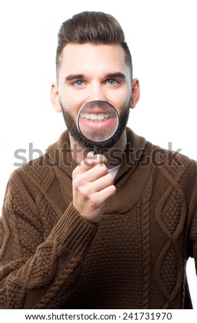 Young attractive man with a magnify glass in front of his mouth - stock photo