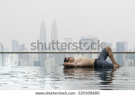 young attractive man with sunglasses on the swimming pool in roof at skyscraper. Is in Kuala Lumpur - stock photo