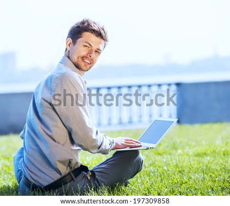 Young attractive man working on laptop outdoor