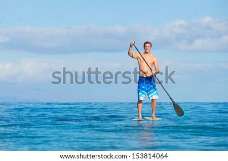 Young Attractive Mann on Stand Up Paddle Board, SUP, in the Blue Waters off Hawaii, Active Life Concept - stock photo