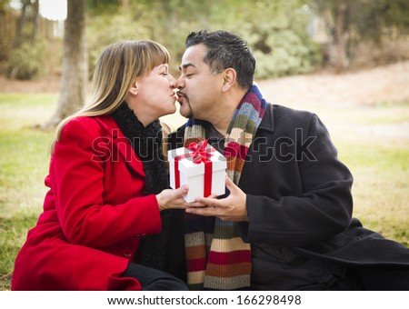 Young Attractive Mixed Race Couple Sharing Christmas or Valentines Day Gift in the Park. - stock photo