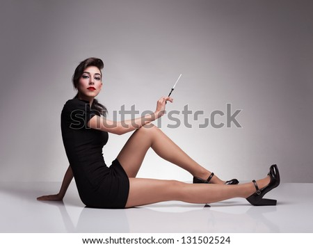 young attractive model sitting on a reflective surface and looking at camera with her blue eyes on grey background - stock photo