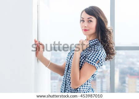 Young attractive model with fit body posing in light studio, wearing jeans and blue checkered shirt, standing sideways - stock photo