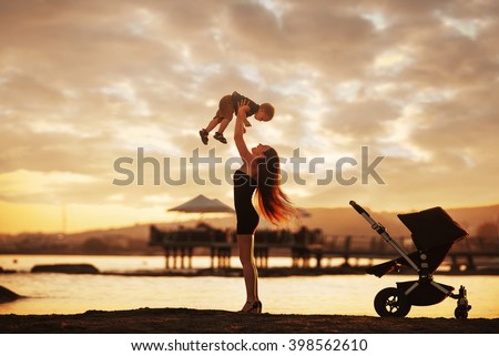 Young attractive mother and her baby boy having fun at sunset on the beach.  - stock photo